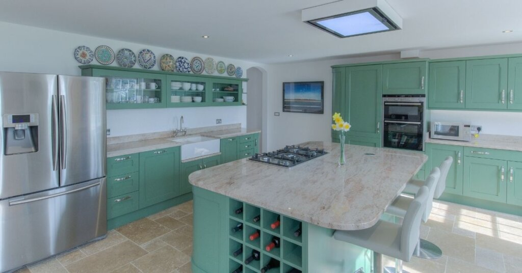 green kitchen with curved island from kestrel kitchens
